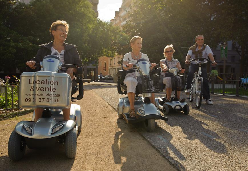 Un groupe de retraités pose avec tous les modèles de scooters et vélos électriques dans un parc