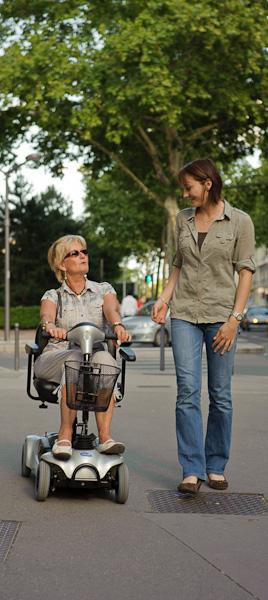 Une femme retraité se balade en discutant sur son scooter électrique au côté d'une jeune femme