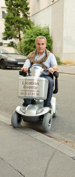 Un homme retraité monte un trotoir avec son scooter électrique