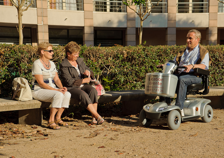 Un homme retraité sur son scooter électrique discute avec deux femmes retraitées assises sur un banc publique