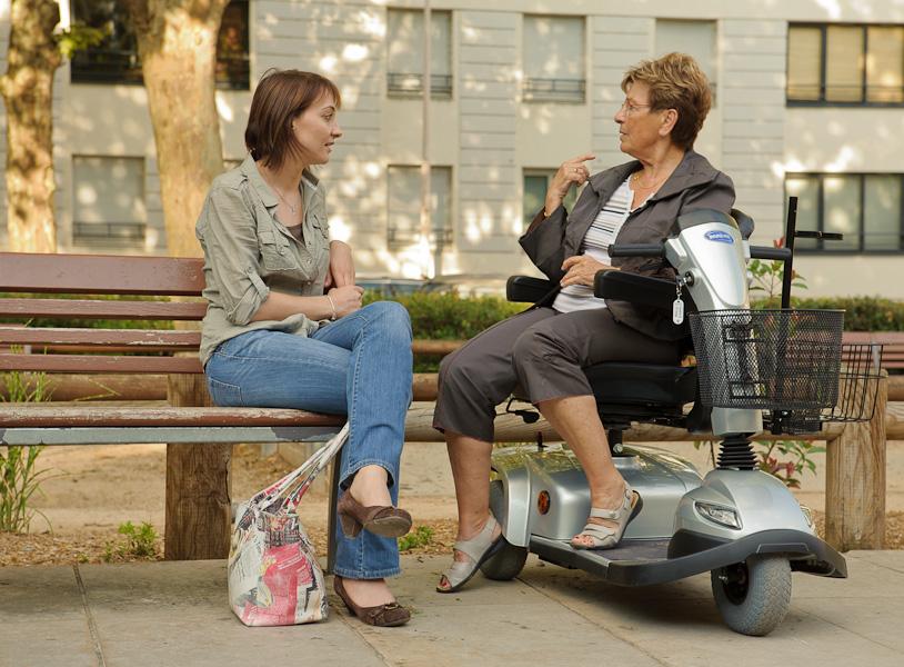 Une jeune femme assise sur un banc discute avec une femme retraité assise sur son scooter électrique