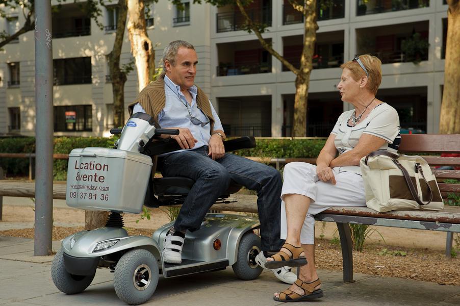 Un homme retraité branché assis sur son scooter électrique drague une femme retraitée dans un parc publique