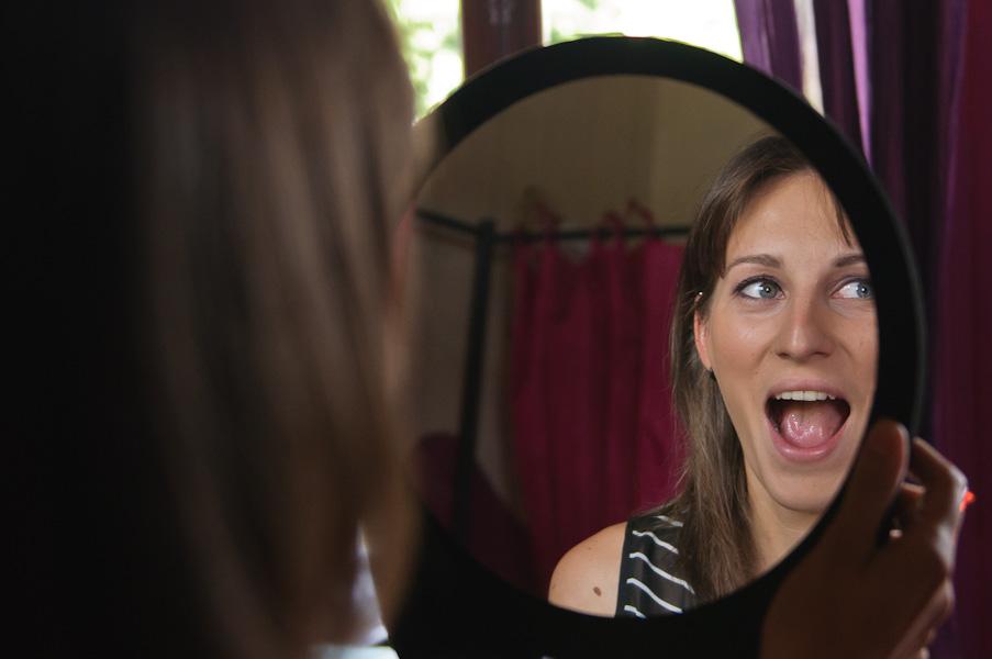 Portrait d'une jeune femme surprise en se voyant maquillée dans un mirroir