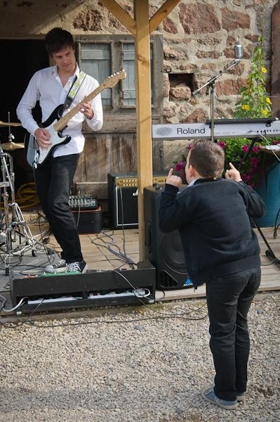 Portrait d'un jeune garçon faisant les cornes devant un guitariste