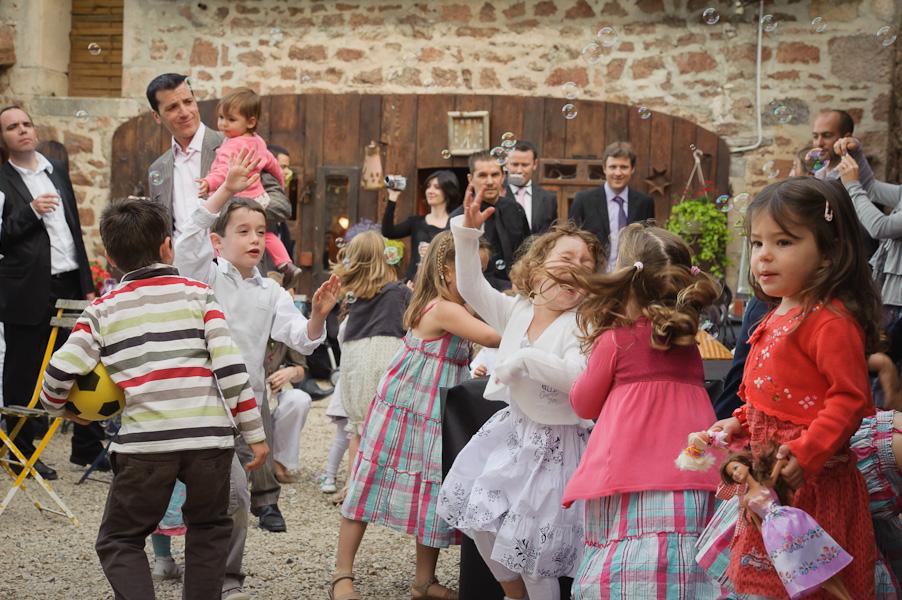 Un groupe d'enfant faisant les fous avec une machine à bulles