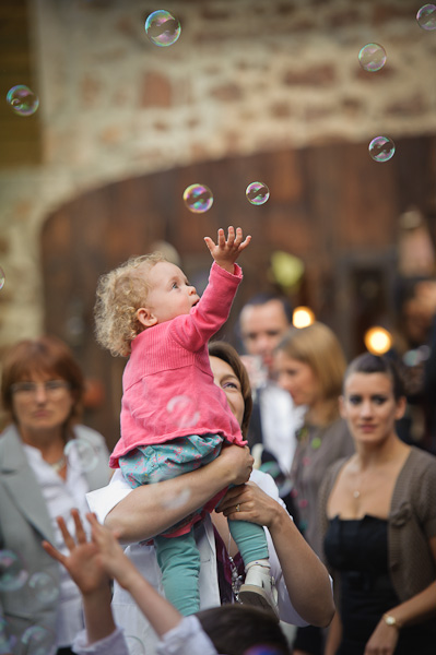 Une enfant dans les bras de sa maman emerveillée par des bulles de savon