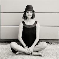 Une jeune femme assise en tailleur avec un chapeau noir