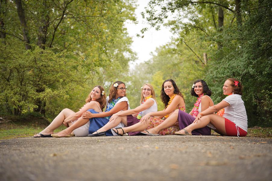 Portrait d'un groupe de copines assises les unes derrière les autres en travers d'un chemin