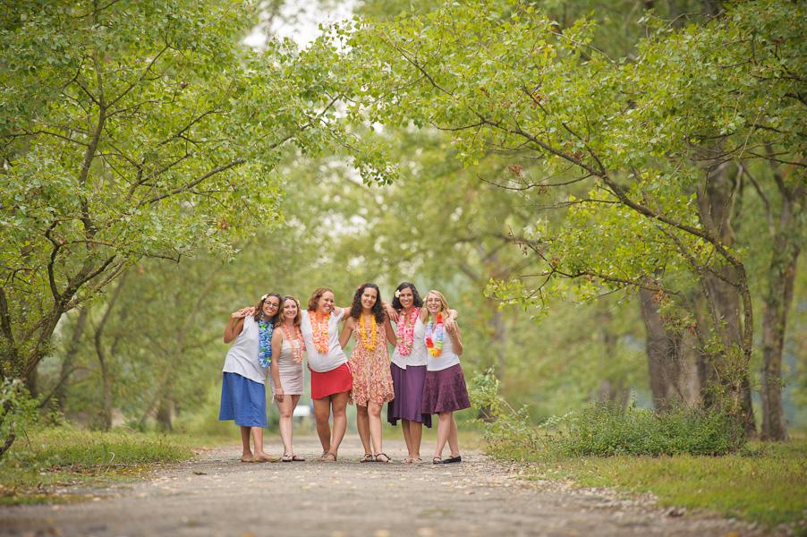 Portrait d'un petit groupe de copines se tenant par les épaules sous une arche boisée