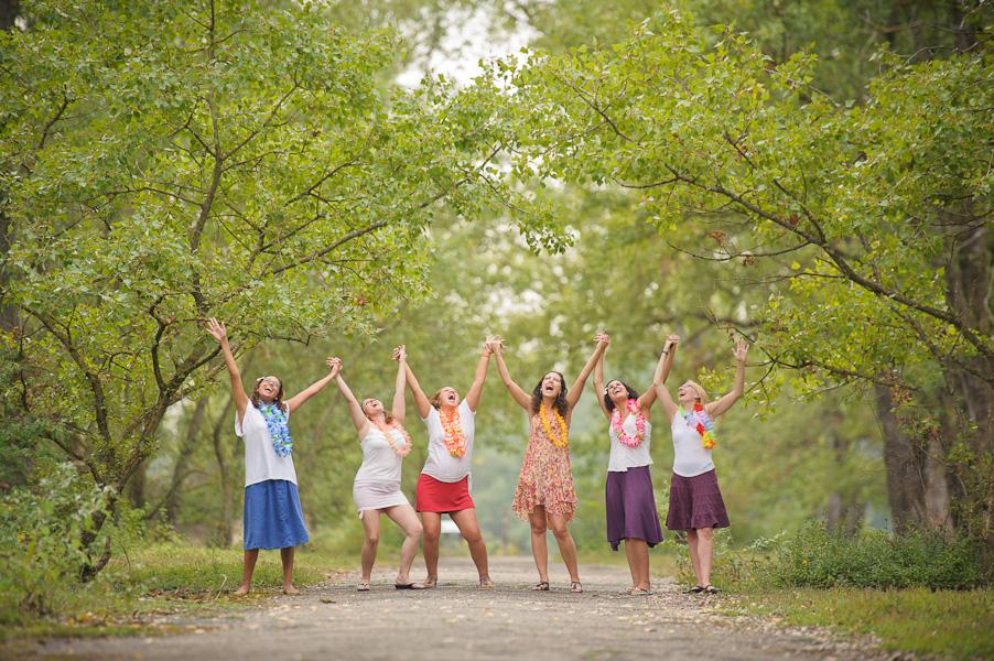 Portrait d'un petit groupe de jeunes femmes levant les bras au ciel en criant sous une arche boisée