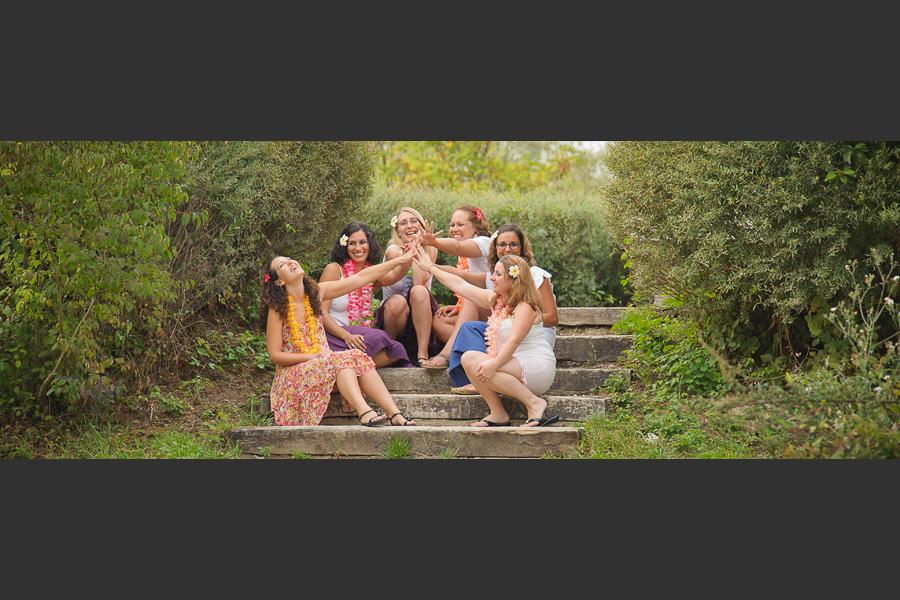 Portrait d'un groupe de copines riant en faisant un high five assises sur un escalier