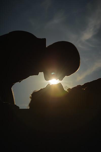 Portrait d'un jeune couple s'embrassant en contre jour au couché du soleil