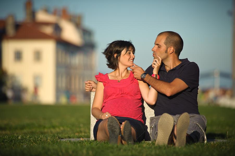 Portrait d'un couple jouant à je te tiens par la barbichette assis dans l'herbe