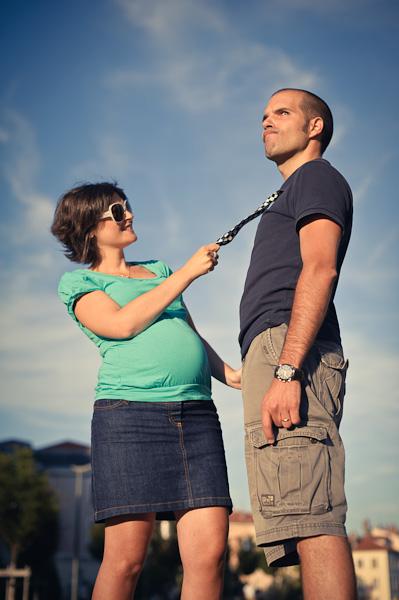 Portrait en contre plongée d'une femme enceinte tenant son mari fier par la cravatte