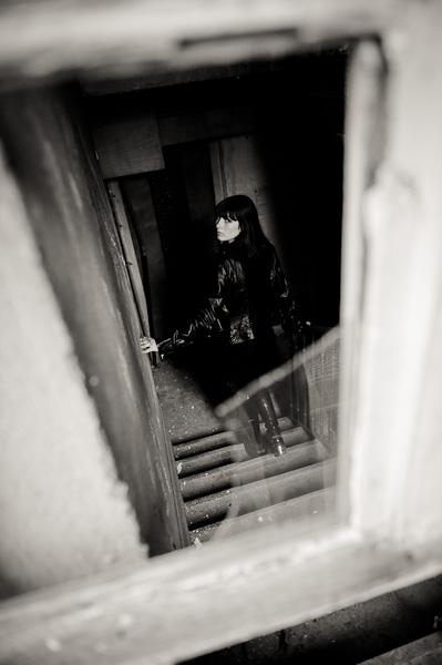 Vision subjective d'une personne espionnant une jeune femme descendant les escaliers