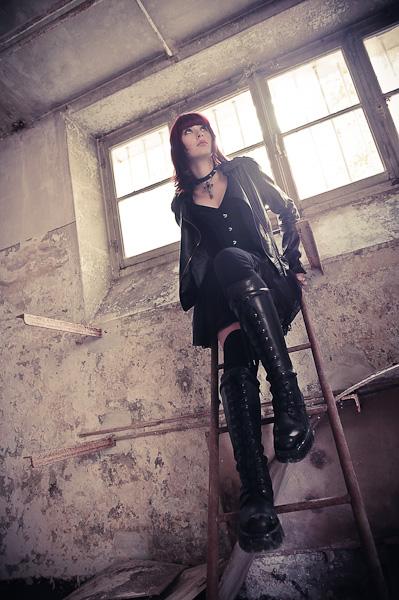 Portrait d'une jeune femme gothique assise sur une echelle en contre plongée
