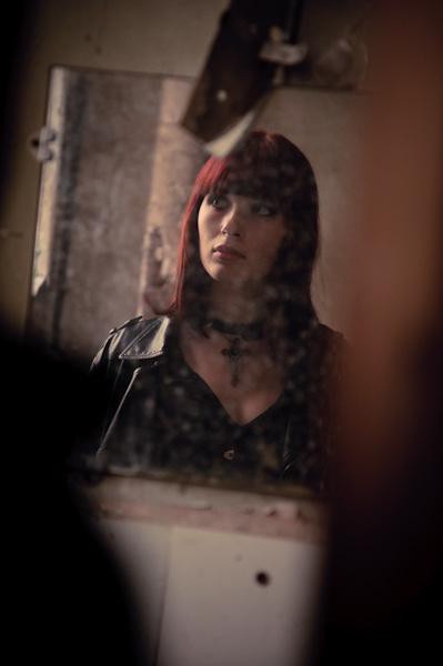 Reflet d'une jeune femme rousse se regardant dans un mirroir salis par le temps