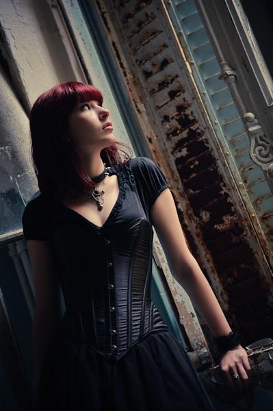 Portrait d'une femme gothique rousse regardant par un vieille fenêtre aux volets rouillés