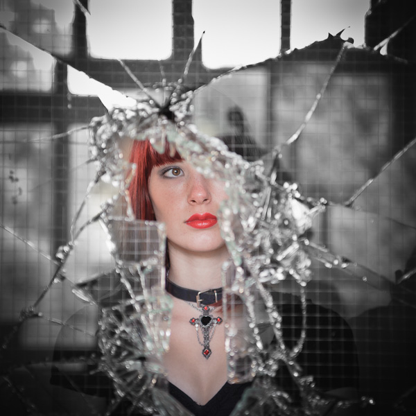 Portrait d'une jeune femme rousse à travers l'éclat d'une fenêtre brisée en désaturation partielle