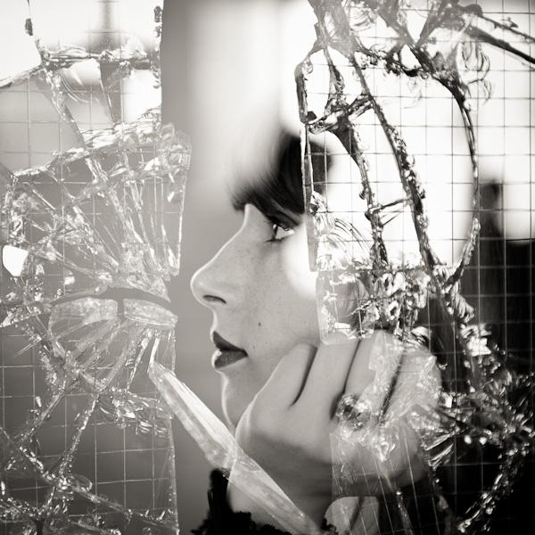 Double exposition d'un portrait d'une jeune femme avec un eclat de vitre brisée en noir et blanc