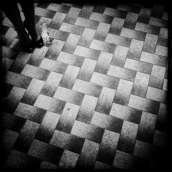 iphonographie avec hipstamatic d'un sol à careaux avec les pieds d'une jeune femme