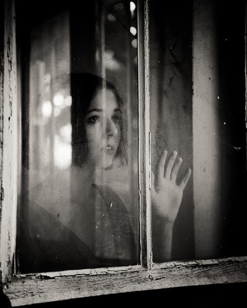 Portrait d'une jeune femme effrayée, enfermée derrière une vitre sale