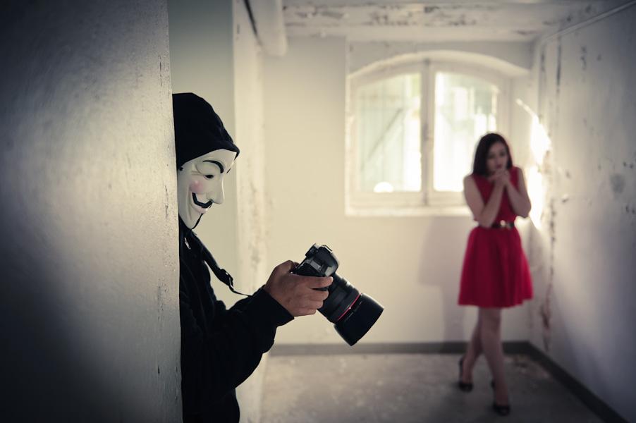 Portrait d'un photographe avec un masque de V pour Vendetta et d'une jeune femme en rouge