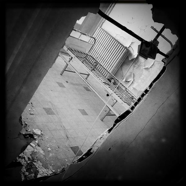 iphonographie avec hipstamatic - vue d'un vieux lit d'hopital à travers un trou dans un mur défoncé