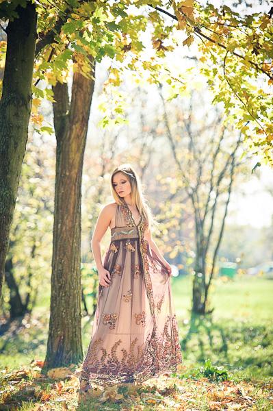 Portrait d'une jeune femme modèle dans les sous bois portant une robe de créateur