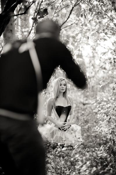 Backstage d'un photographe en pleine séance shooting avec une jeune modèle blonde en corset