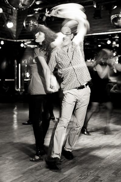 Un couple de danseurs de salsa en pleine passe sur une piste de danse