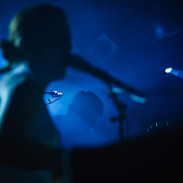Silhouette de la chanteuse encadrant le bassiste perdu dans un écran de fumée bleue