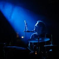 Portrait du batteur éclairé tel un messie par un faiseau de lumière bleue venant du ciel