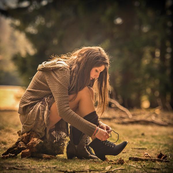 Portrait d'une jeune femme brune au milieu d'un clairière enfilant sa chaussure