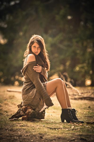 Portrait d'une jeune modèle assise sur une souche d'arbre près d'une forêt