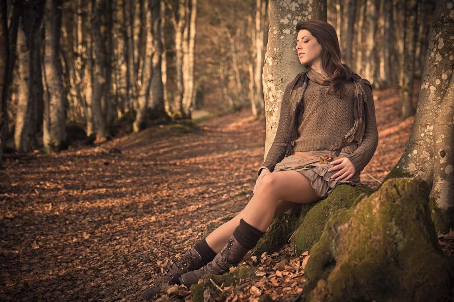 Portrait d'une jeune femme allongée contre un arbre dans une forêt au couché du soleil