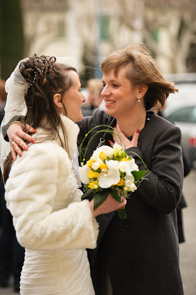 Portrait de la future mariée salué par l'une de ses invités devant la mairie
