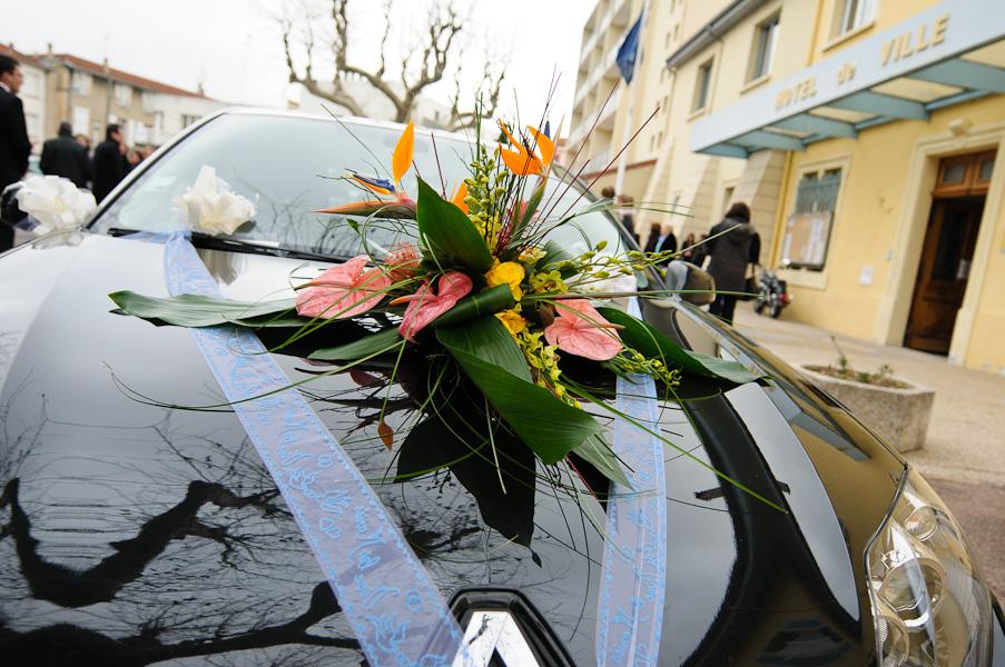 gros plan du bouquet décorant la voiture des futurs époux garée devant l'hôtel de ville