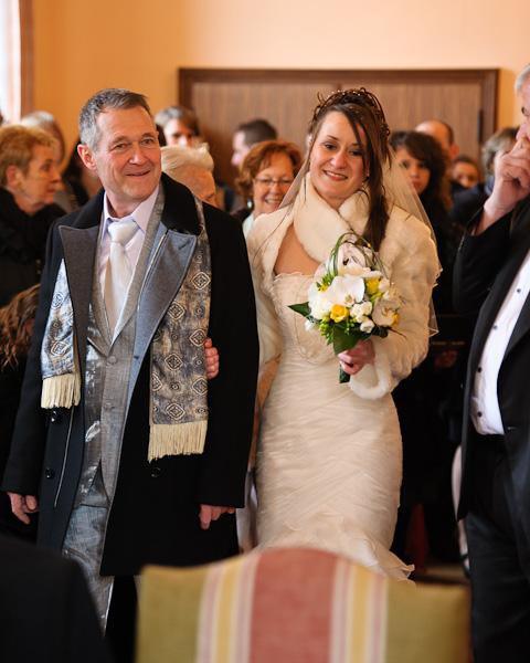Portrait de la mariée au bras de son papa à l'entrée de la mairie