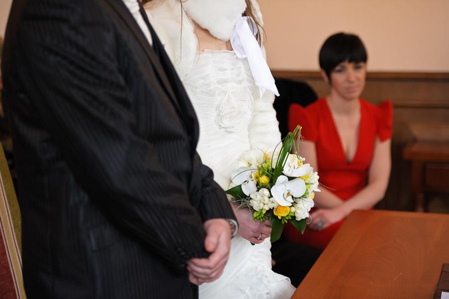 Gros plan sur les mains des futurs époux avec le bouquet de la mariée et une témoin en arrière plan