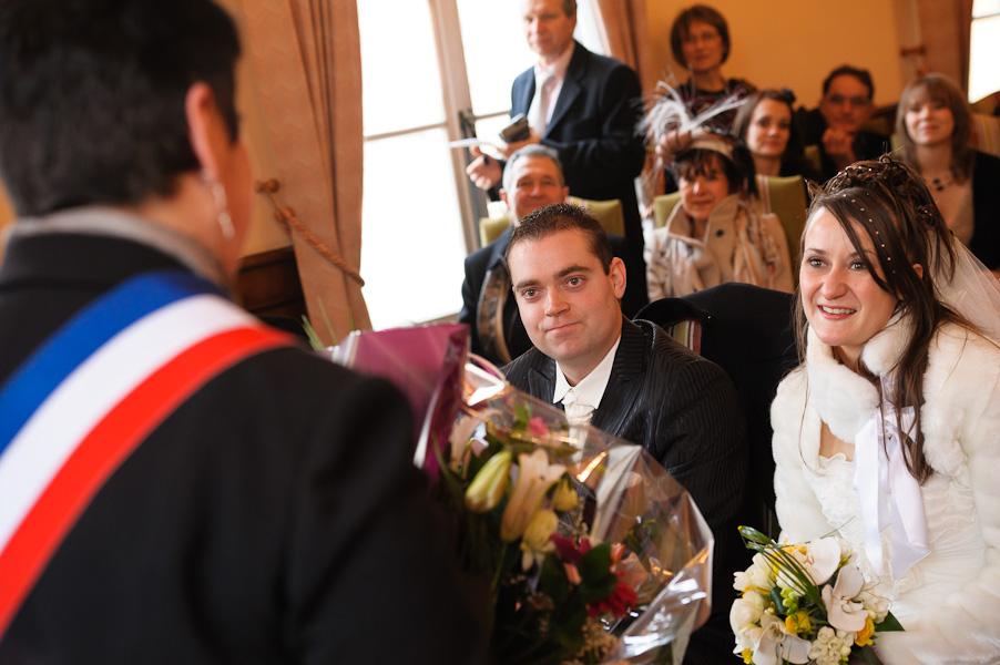 Portrait des deux mariés se faisant offrir un bouquet de fleurs par madame le maire