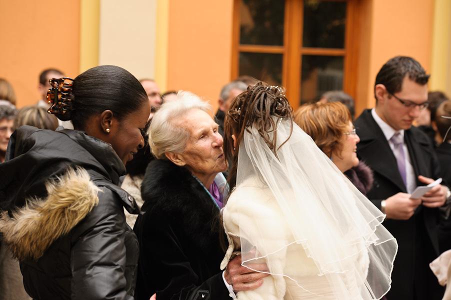 Portrait de la grand-mère embrassant la mariée à la sortie de l'église