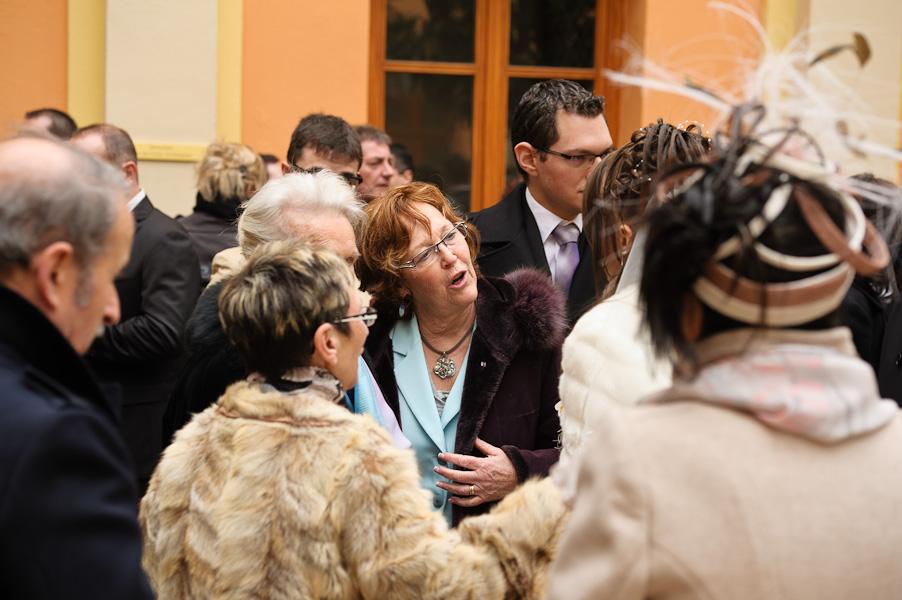 Portrait d'un groupe d'invités rassemblés autour de la marié à la sortie de la mairie