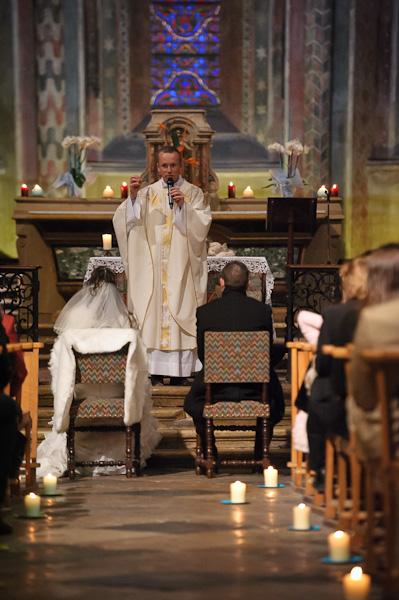 Portrait du curé officiant en face des deux mariés vu depuis l'allée de l'église