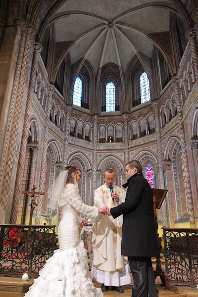 Portrait en contre plongée du prêtre et des mariés échangeant les alliances avec la chapelle du Saint Sacrement en arrière plan