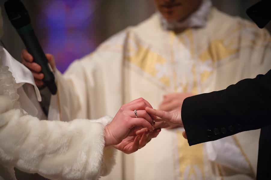 Gros plan sur la marié passant l'alliance au doigt de son mari