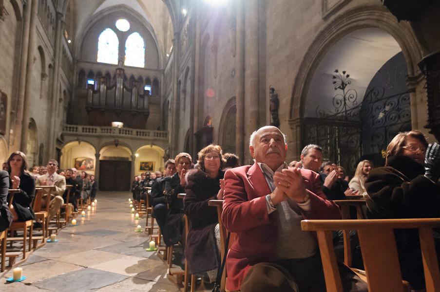 Vue du fond de l'église avec les invités applaudissant les nouveaux mariés