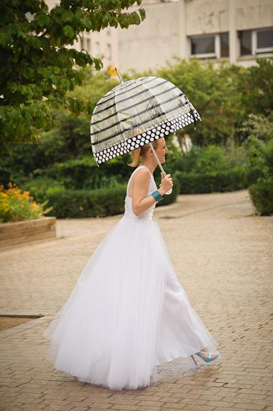 Portrait de la mariée marchant vers la mairie avec un parapluie transparent