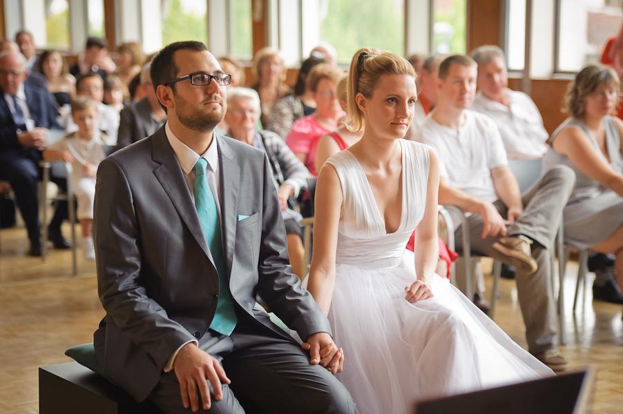Portrait des deux époux se tenant la main assis devant le maire avec leur invités en arrière plan