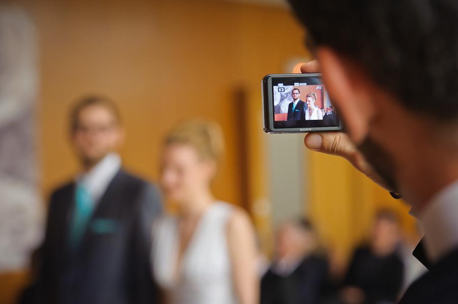 Portrait d'un invité prenant les mariés en photo avec son compact